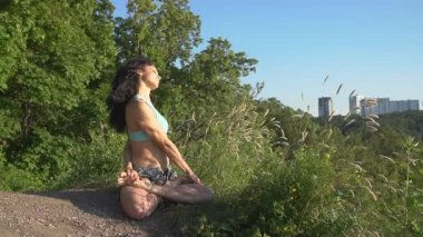 Healthy woman meditating in pose lotus over at sunset. Slow Motion