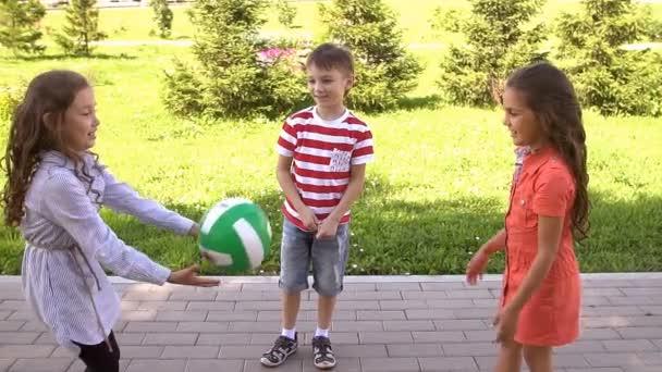 Gruppe fröhlicher Kinder, die draußen im Sommerpark spielen. Zeitlupe