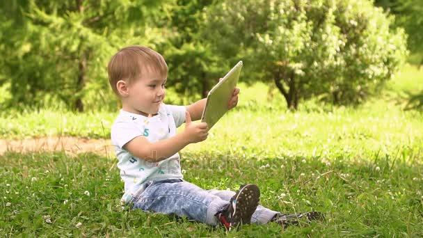 Fiatal baba fiú használ tabletta számítógép kívül a Park.
