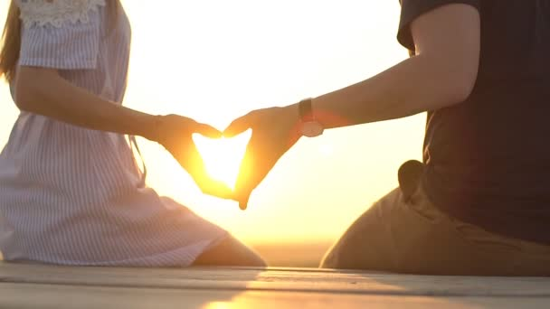Romantic Man and Woman join hands in a heart shape against the sun. Love and affection.