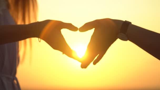 Fiatal pár Térkép Szív jelet naplementekor, Silhouette. Lassú mozgás.