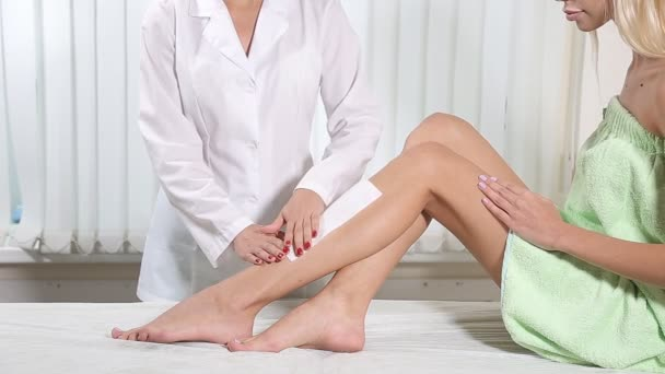 Beautician removing leg hair with wax.