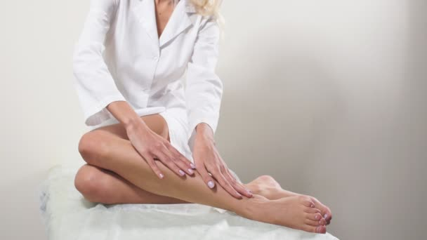 The young woman with perfect body is sitting with smooth silky legs after depilation. Concept of depilation, smooth skin, skincare, cosmetics, wellness center,healthy lifestyle.