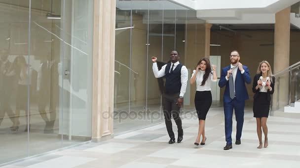 Zpomalený pohyb. Obchodní lidí chodících chodbou úřadu a slaví vítězství
