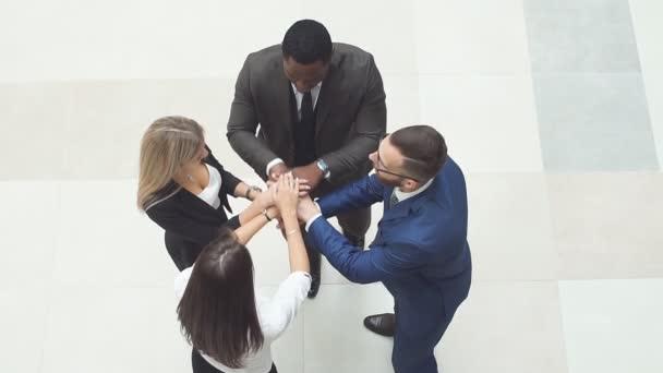 Obchodní lidé dělají team building, pak uvedení ruce nad všechny ostatní. Zpomalený pohyb