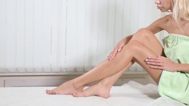 Giovane donna è seduta con gambe lisce come la seta dopo depilazione.