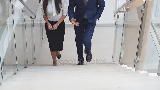 Business partners climb the stairs of the office building communicating with each other