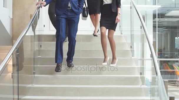 Skupina podnikatelů sestupuje po schodech po práci