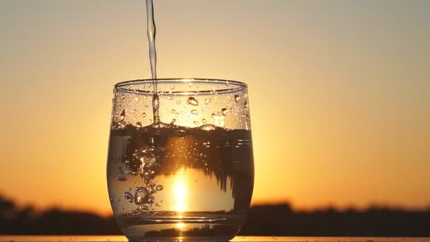 Glas bei Sonnenuntergang mit Wasser füllen, Zeitlupe