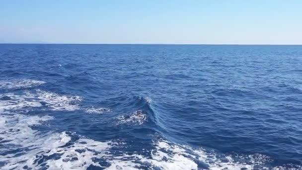 Loď probuzení do oceánu. Pěnové stopy za velkou loď vody jde až k obzoru. Zpomalený pohyb
