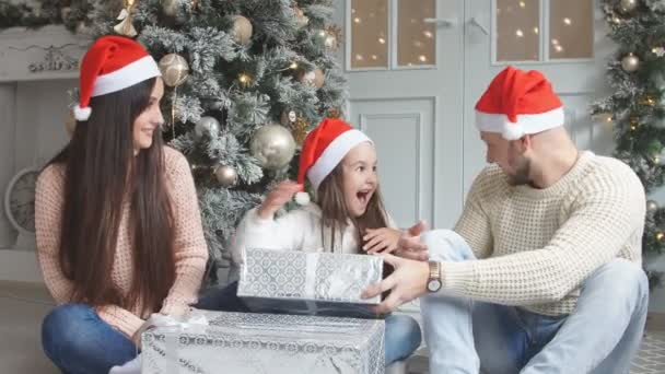 Parents and young girl having fun together near Christmas tree.