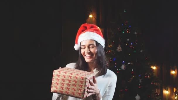 Šťastná dívka v klobouku Santa Claus s dárky v ruce. Zpomalený pohyb