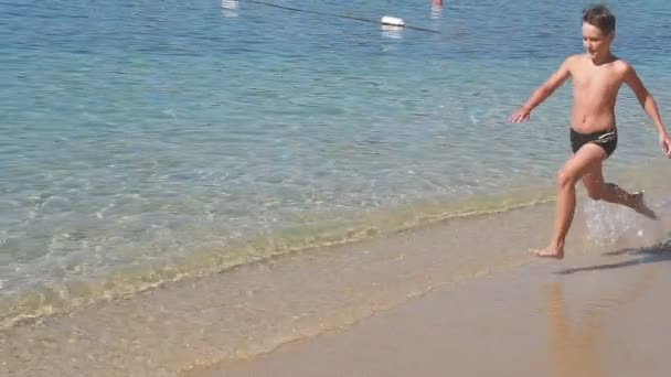 Boy is running on the beach, raises splashes. Slow Motion