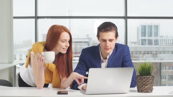 mladí podnikatelé, pracující na přenosný počítač v kanceláři.