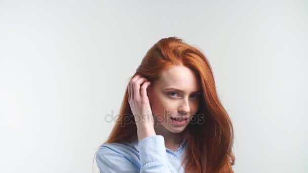 Portrét pěkně mazaná holka s úsměvem při pohledu na fotoaparát.