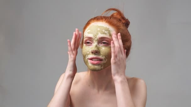 Krásná rusovláska dívka použití obličejové jílová maska. Kosmetické procedury. Šedé pozadí. Zpomalený pohyb