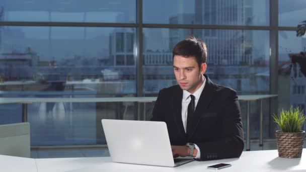 Businessman in office with laptop computer.