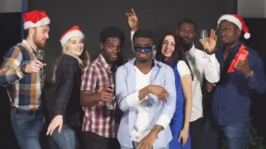 Multi ethnic group friends dancing and having fun at Christmas party.