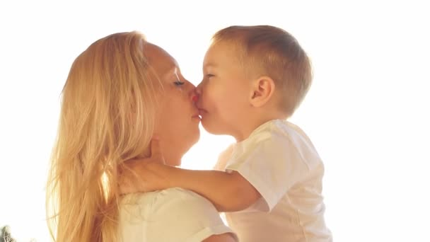 Happy mother and son laughing and kissing at sunset. Slow motion