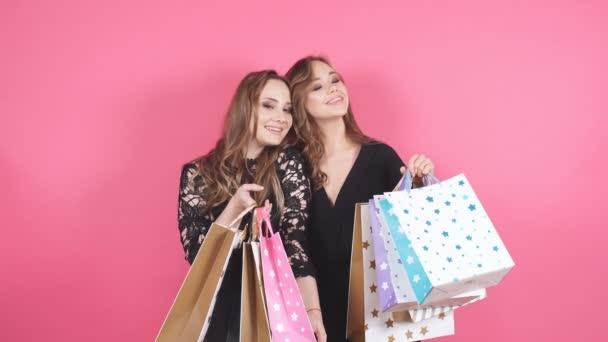 Dvě krásné usmívající se dívka s mnoha nákupní tašky.