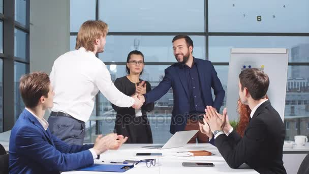 Business people shaking hands at interview while others clap at the office.