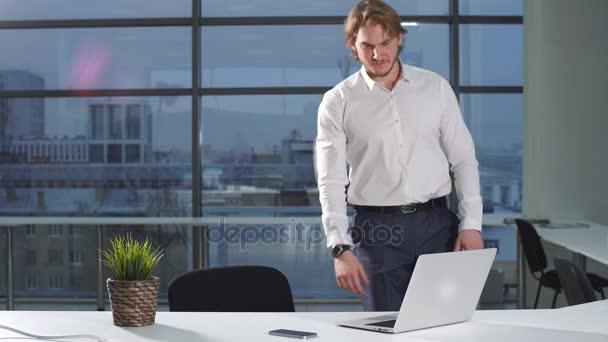Portrét mladé atraktivní podnikatel pracuje u stolu, použití přenosný počítač v kanceláři.