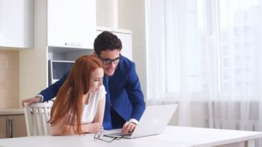 Young business couple talking and using tablet in kitchen at home.