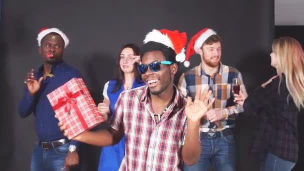 Eine gemischte Gruppe junger Leute auf einer Weihnachtsfeier. Zeitlupe