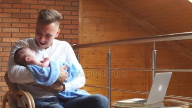 Young father rocking his adorable baby son while working on computer at home.