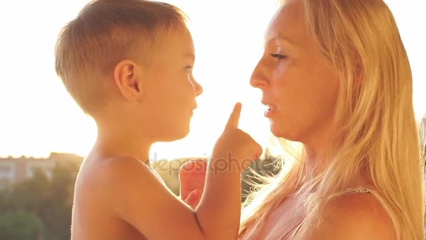 Young mother playing with baby son at sunset. Slow Motion