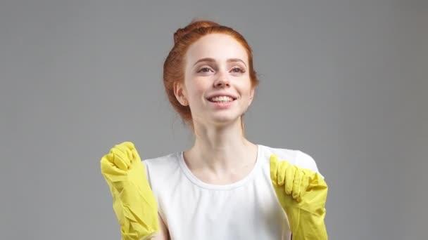 Porträt einer jungen Frau in Gummihandschuhen blickt lächelnd in die Kamera. Konzept der Reinigung, Sauberkeit.