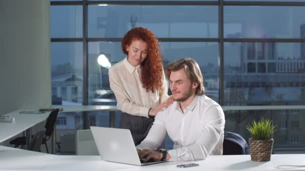 Young business couple working with laptop in office.