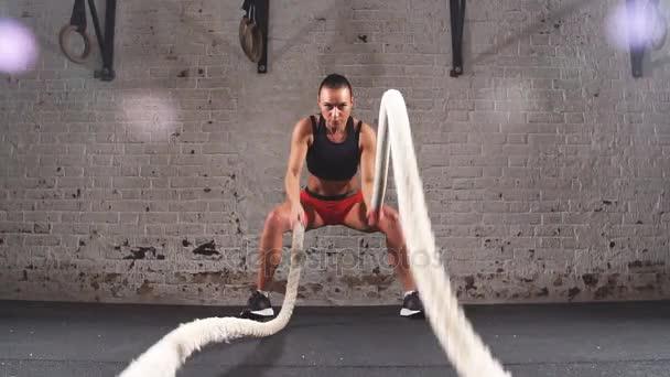 Sportovní žena aktivně v tělocvičně cvičení s bitva lana během její Cross Fitness cvičení. Zpomalený pohyb