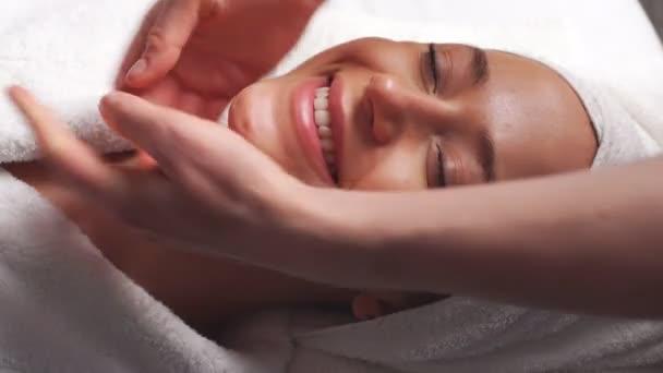 Lázně žena obličejové masáže. Masáž obličeje ve spa salonu krásy. Žena se těší relaxační masáž obličeje v kosmetologii lázeňském centru. Péče o tělo, kosmetika, wellness, kosmetické ošetření