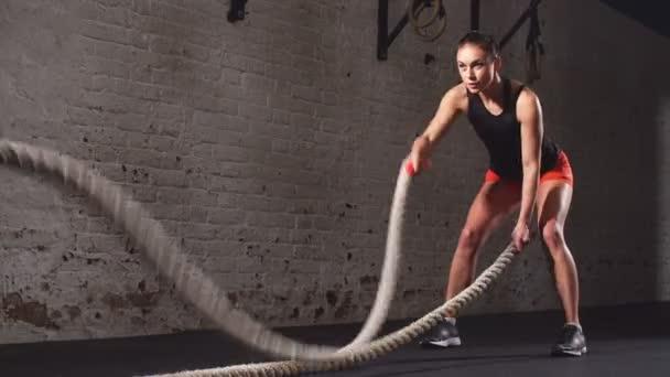 Žena cvičit s bojovými provazy v tělocvičně