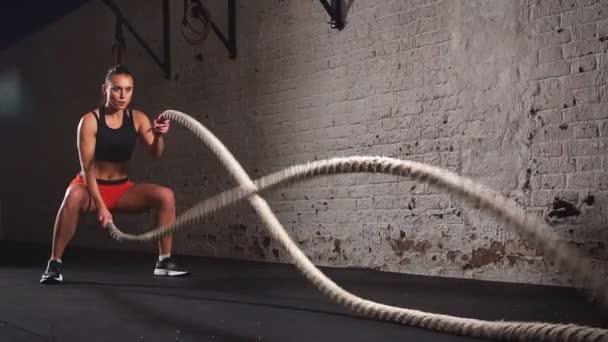 Mladá dospělá žena vykonávající bitva lano cvičení během kříž fit cvičení v tělocvičně. Zpomalený pohyb