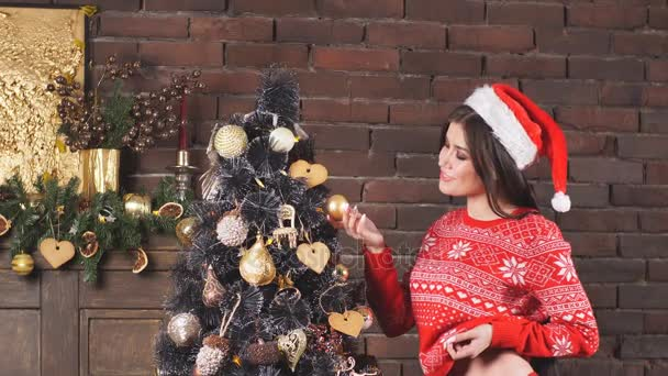 verführerisches Mädchen in roter Dessous und rotem Pullover geschmückter Baum.