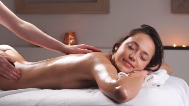 Gyönyörű nő pihentető spa szalonban forró kövek a testen. Szépségkezelés.
