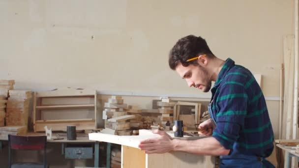mladý tesař, zatloukání hřebíku do dřevěné desky.