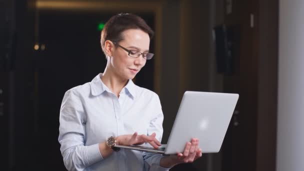 Businesswoman wearing Glasses Holding Laptop Computer in office hall.