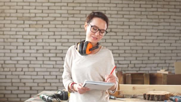 Portrét šťastný atraktivní pracovitý profesionální zaměstnankyně s pero a tablet v dílně