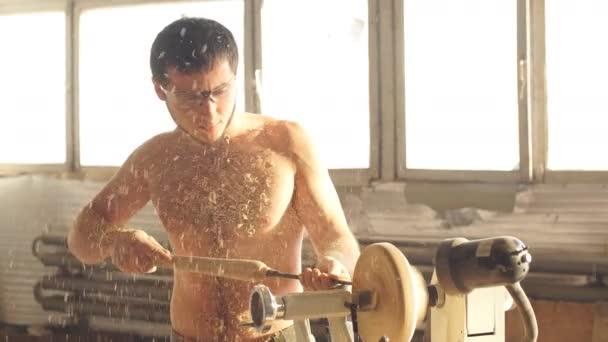 nahý muž carpentering v dílně a pomocí malé ruční soustruh