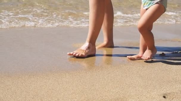 Glückliche Familie am Strand. Mutter und Sohn spazieren am Meeresufer entlang. Zeitlupe.