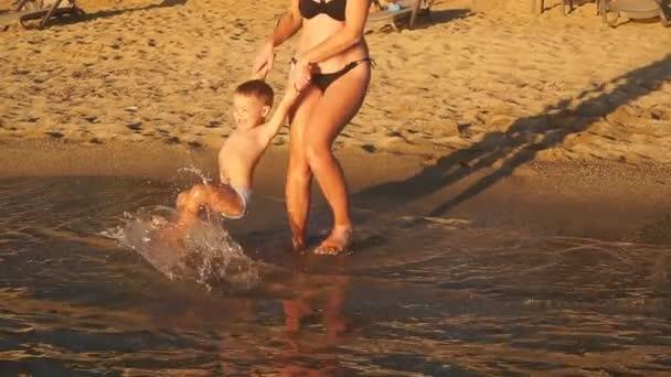 glückliche junge Mutter spielt mit ihrem Sohn im Meer, lächelt und lacht.