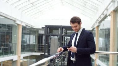 Happy attractive young businessman walking and using mobile phone indoors.