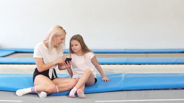 Matka a dívka pomocí telefonu v tělocvičně pro sledování video jak udělat skákání cvičení