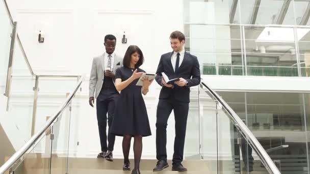 Členové finanční mnohonárodnostní týmu jít dolů po schodech s tablety a chytrými telefony