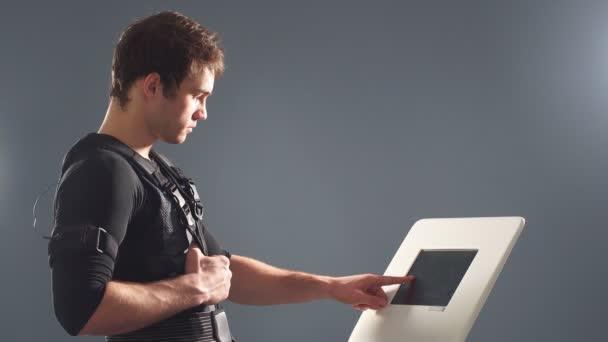 EMS, portrét pohledný muž blízko Elektro svalové stimulace stroj