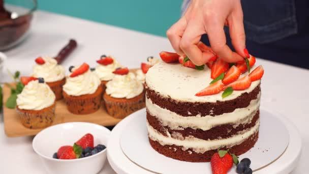 Cukrář žena je zdobení Delicious dort ve studiu.