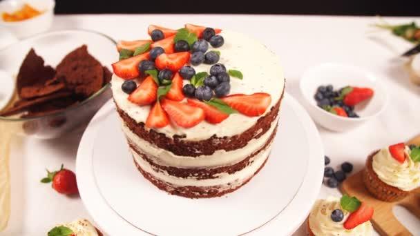 Cafe-chef díszíti a tortát. Eper- és puding torta.